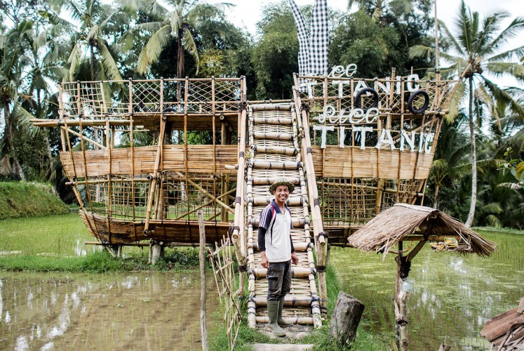 Ride the ship: Nyoman Wastu creates his own tourist attraction from bamboo. His paddy field is located far from the main street, so he has to make an effort to attract tourists.