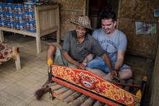 Percussion sounds: Wayan Kantun shows a French tourist how to play a traditional gamelan instrument in his stall. The farmer lives near the terrace trekking area and sells young coconuts to get additional income.  JP/ Anggara Mahendra