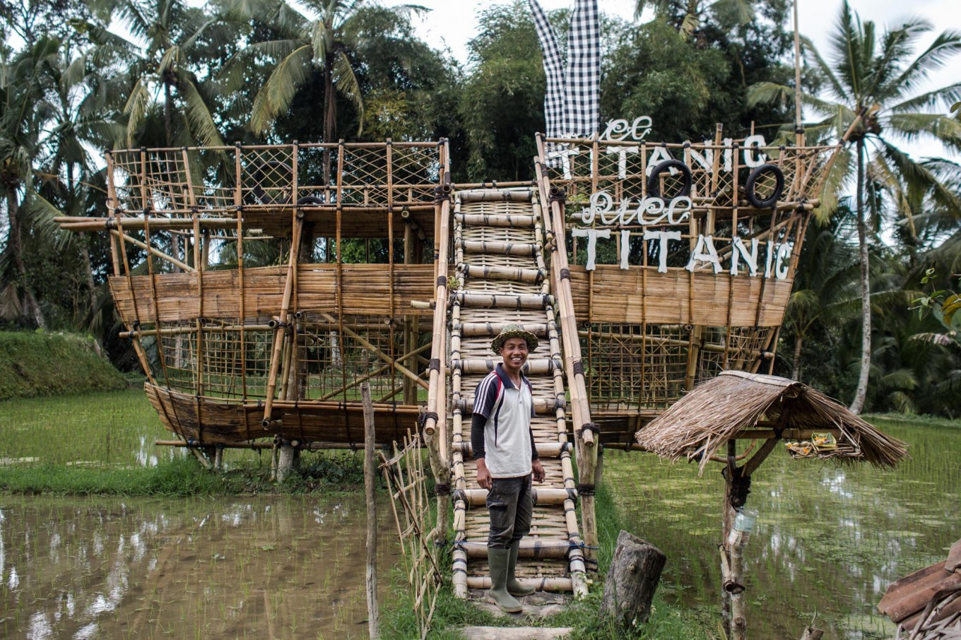 Ride the ship: Nyoman Wastu creates his own tourist attraction from bamboo. His paddy field is located far from the main street, so he has to make an effort to attract tourists. JP/ Anggara Mahendra