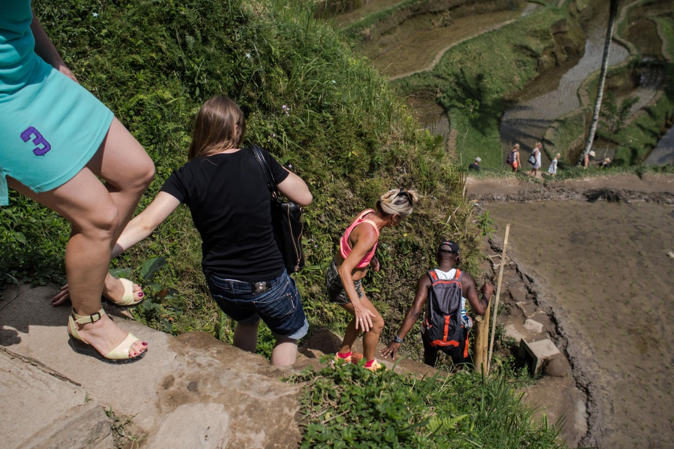 Step by step: Foreign tourists climb down the paddy terrace wall in Ceking. JP/ Anggara Mahendra