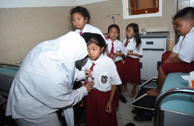 Take a deep breath: A health worker checks the condition of a student from state elementary school SDN Pandanrejo in Batu city, East Java, at community health center Puskesmas Bumiaji, on Sept.6.