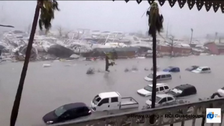 A handout grab image made from a video released on September 6, 2017 by RCI.fm shows flooded streets and damage on the French overseas island of Saint-Martin, filmed from a terrace of the Beach Plaza hotel after high winds from Hurricane Irma hit the island.