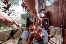 A girl receives holy water from a priest during the Tumpek Pengatag ceremony and drinks it. JP/Anggara Mahendra