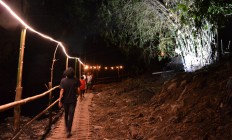 The festival's guests and visitors walk along a riverbank path lit with lamps to reach the JenesRiver Festival venue, coming face-to- face with the polluted river.JP/Stefanus Ajie