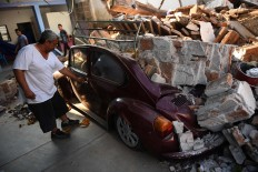 A man tries to open his Beetle's car, crashed by debris from his house which was damaged by a powerful earthquake that struck Mexico's Pacific coast late on September 7, in Juchitan de Zaragoza, Mexico, on September 9, 2017.