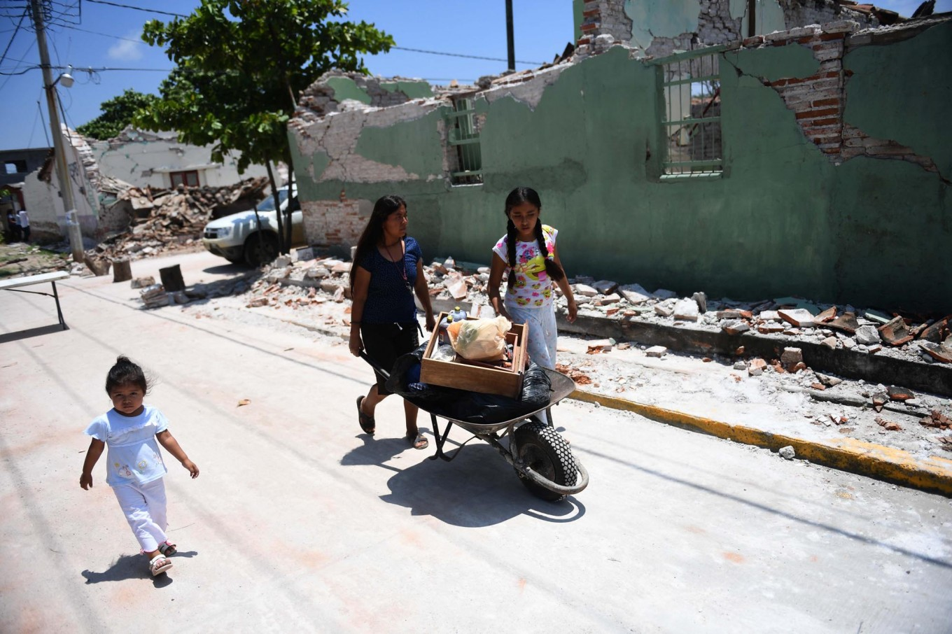 People walk by buildings knocked down by 