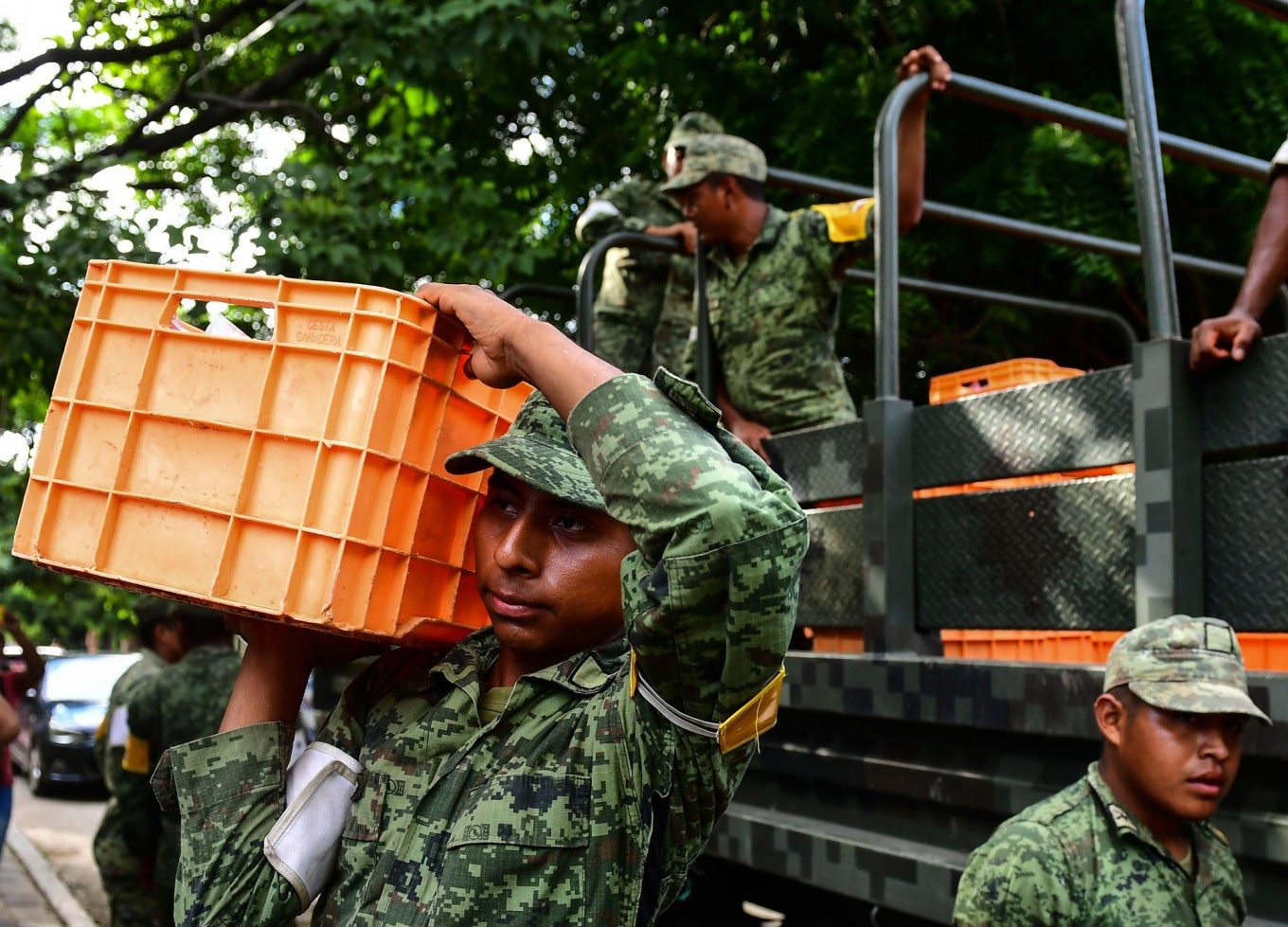 Mexican soldiers unload water in Juchitan  de Zaragoza, state of Oaxaca on September 10, 2017, for those affected by the 8.2 magnitude earthquake that hit Mexico's Pacific Coast on September 8.  Mexican families picked nervously at the  ruins of their homes Sunday as help trickled in after a huge earthquake killed 90 people. People in Juchitan were afraid to return to their homes, fearing the effects of hundreds of aftershocks --  but camped within sight of them to prevent looting.  AFP/ Ronaldo Schemidt
