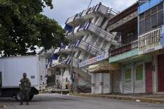 A soldier stands guard a few metres away from the Sensacion hotel which collapsed with the powerful earthquake that struck Mexico overnight, in Matias Romero, Oaxaca State, on September 8, 2017. Mexico's most powerful earthquake in a  century killed at least 35 people, officials said Friday, after it struck the Pacific coast, wrecking homes and sending families fleeing into the streets. AFP/ Ronaldo Schemidt