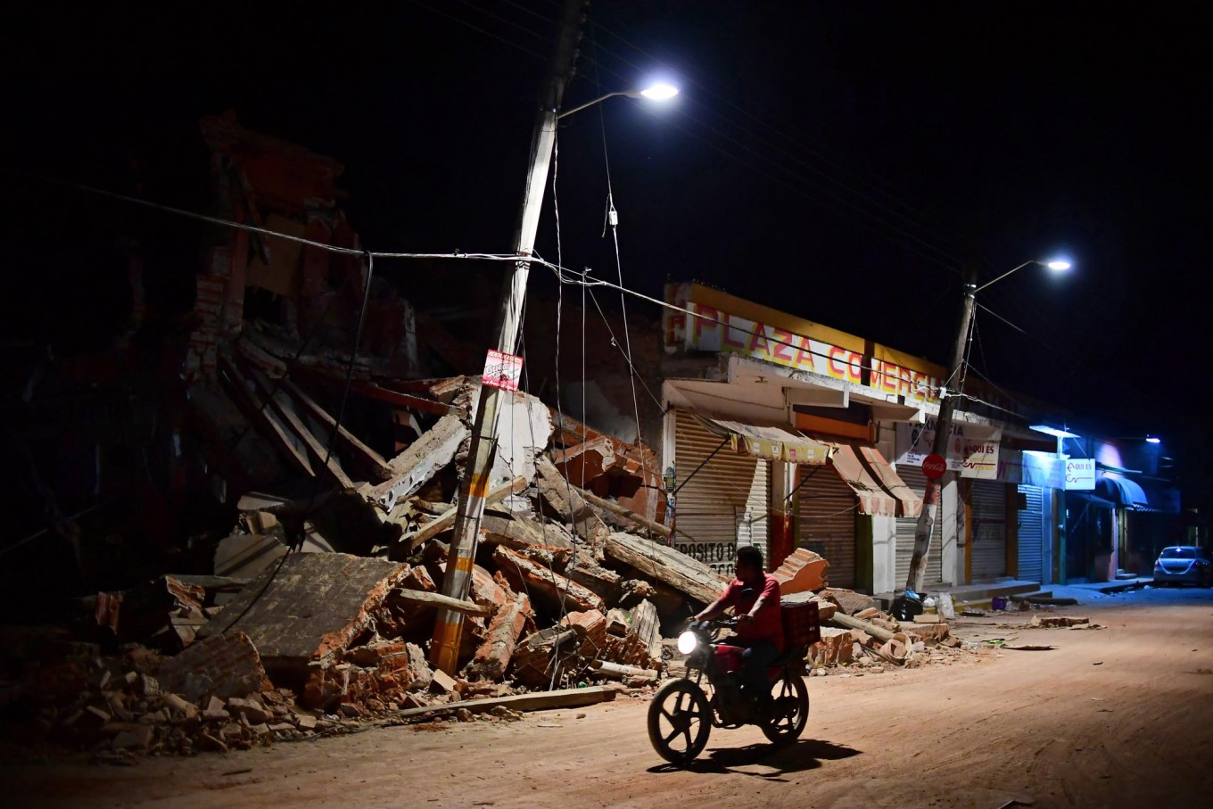 A man rides his motorbike in Juchitan de  Zaragoza, state of Oaxaca on September 9, 2017, the day after an 8.2 magnitude earthquake hit Mexico's Pacific coast, Rescuers pulled bodies from the rubble and grieving families carried coffins through the streets after Mexico's  biggest earthquake in a century killed 65  people, while elsewhere two died in mudslides unleashed by storm Katia. AFP/ Ronaldo Schemidt