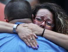 A woman hugs a man during a commemoration ceremony for the victims of the September 11 terrorist attacks at the National September 11 Memorial and Museum fifteen years after the day on September 11, 2016 in New York City. Throughout the country services are being held to remember the 2,977 people who were killed in New York, the Pentagon and in a field in rural Pennsylvania.   AFP/Getty Images/Spencer Platt