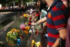 People gather at one of the pools at the National September 11 Memorial following a morning commemoration ceremony for the victims of the terrorist attacks fifteen years after the day on September 11, 2016 in New York City. Throughout the country services are being held to remember the 2,977 people who were killed in New York, the Pentagon and in a field in rural Pennsylvania.   AFP/Getty Images/Spencer Platt