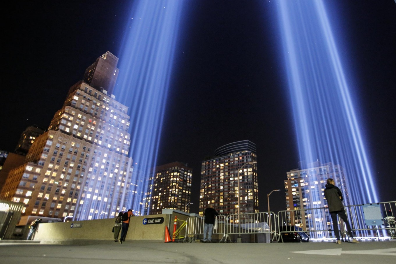 People gather on a rooftop as the 'Tribute in Light' illuminates the night sky, on September 10, 2017 in New York City, on the eve of the anniversary of the September 11, 2001 terror attacks. Commemorations are being held on the 16th anniversary of the 9/11 terror attacks, with President Donald Trump expected to speak at a ceremony for the 184 people killed at the Pentagon in Washington, DC. AFP/ Kena Betancur