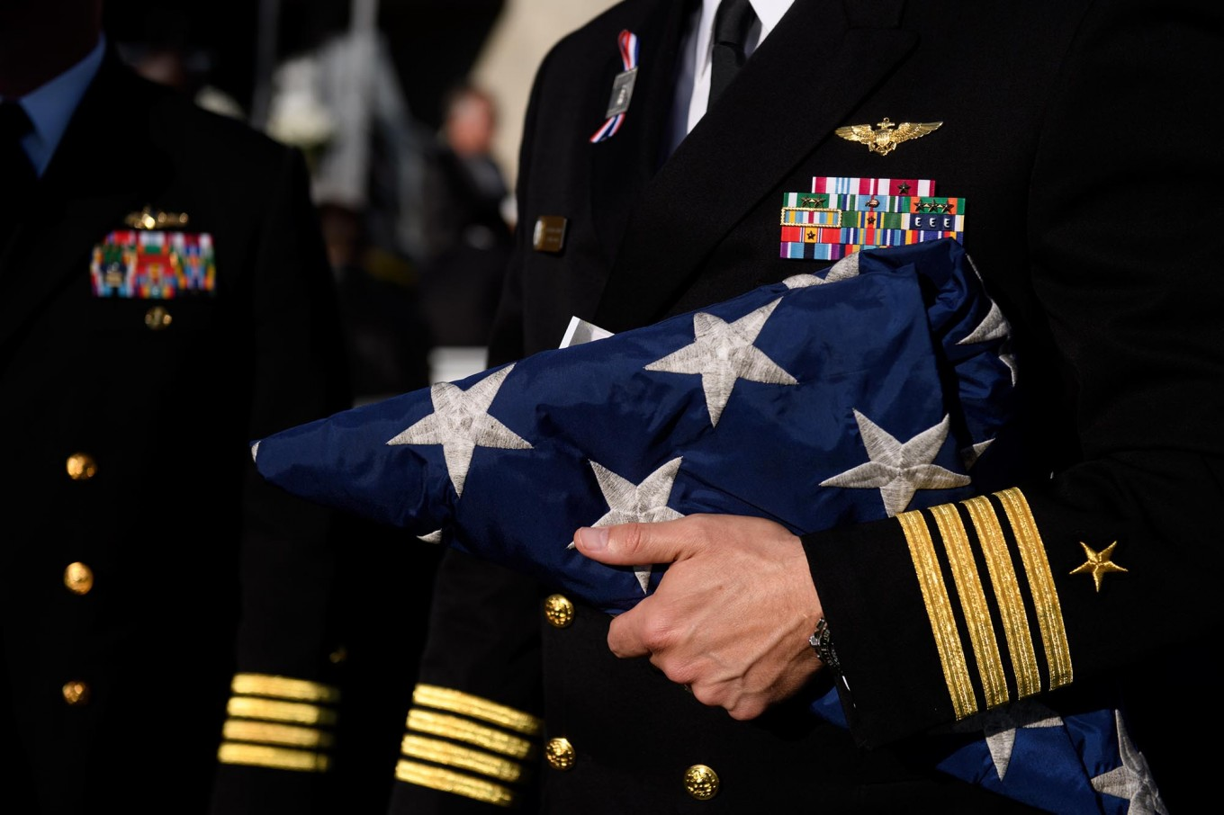 Navy Captain William Sherrod holds a flag from the USS Somerset to present to family members of the the victims at the Flight 93 National Memorial on the 16th Anniversary ceremony of the September 11th terrorist attacks, September 11, 2017 in Shanksville, Pennsylvania. United Airlines Flight 93 crashed into a field outside Shanksville, PA with 40 passengers and 4 hijackers aboard on September 11, 2001. AFP /Getty Images/Jeff Swensen