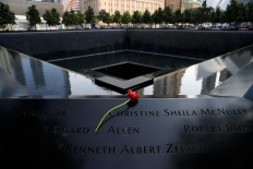 A flower is left at the North pool during a commemoration ceremony for the victims of the September 11 terrorist attacks at the National September 11 Memorial, September 11, 2017 in New York City. In New York City and throughout the United States, the country is marking the 16th anniversary of the September 11 terrorist attacks.  AFP/Getty Images/Drew Angerer