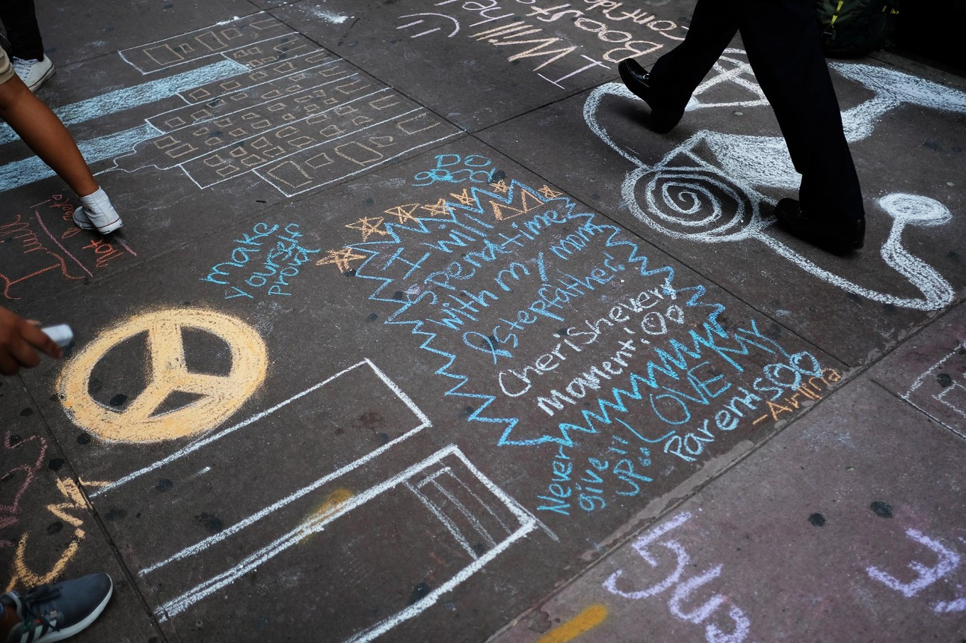 High school students draw the Twin Towers and write messages on the sidewalk in front of their school on September 11, 2017 in New York, in observance of 16th anniversary of the September 11, 2001 attacks. The attack, deadliest ever on US soil, killed 2,997 people, and plunged the United States into a chain of rolling wars against Islamic militants.  AFP/ Jewel Samad