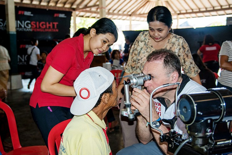 Eye check: UK ophthalmologist Tony Moriarty (right) examines a patient during his time in Bali as a volunteer consultant accompanying the John Fawcett Foundation's team and local ophthalmologists on village visits.