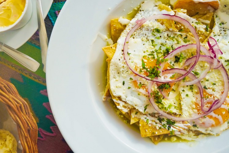 The dish 'chilaquiles' is made from 'totopos' or nachos chips topped with cheese, sauce and other toppings.