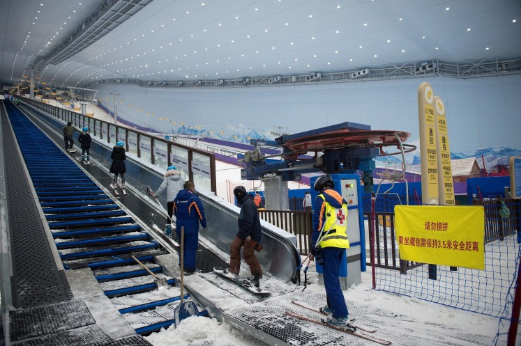 In this picture taken on August 22, 2017, people use a snow escalator at the Wanda Harbin Ice and Snow Park in Harbin. At Dalian Wanda Group's new Ice and Snow Park, chilly winds blew snowflakes around skiers zipping down the manmade slopes of the world's largest indoor ski park, a potent symbol of China's ambitions to turn itself into a winter sports powerhouse ahead of the 2022 Winter Olympics in Beijing.