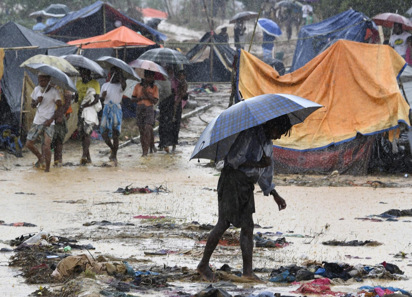 A Rohingya refugee holds an umbrella during rain in Bangladesh's Balukhali refugee camp on September 17, 2017. Monsoon rain amid a drive to move hundreds of thousands of Muslim Rohingya out of makeshift camps added to the misery of the refugees on September 17 who have fled violence in Myanmar for Bangladesh. AFP/ Dominique Faget
