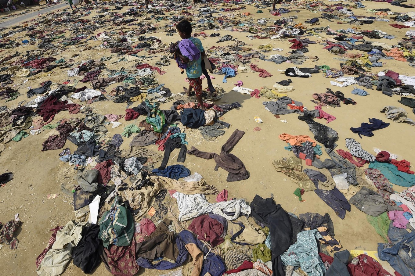A Rohingya Muslim boy walks past discarded clothing on the ground at the Bhalukali refugee camp near Ukhia on September 16, 2017. According to the UN nearly 400,000 Rohingya have arrived in Bangladesh since August 25 after fleeing a military crackdown launched by Myanmar's military in response to attacks by Rohingya rebels. AFP/ Dominique Faget