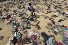 A Rohingya Muslim boy walks past discarded clothing on the ground at the Bhalukali refugee camp near Ukhia on September 16, 2017.