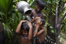 Young Rohingya refugees wash themselves at the Jalpatoli refugee camp in the no-man's land area between Myanmar and Bangladesh, near Gumdhum village in Ukhia on September 16, 2017. According to the UN nearly 400,000 Rohingya have arrived in Bangladesh since August 25 after fleeing a military crackdown launched by Myanmar's military in response to attacks by Rohingya rebels. AFP/ Dominique Faget
