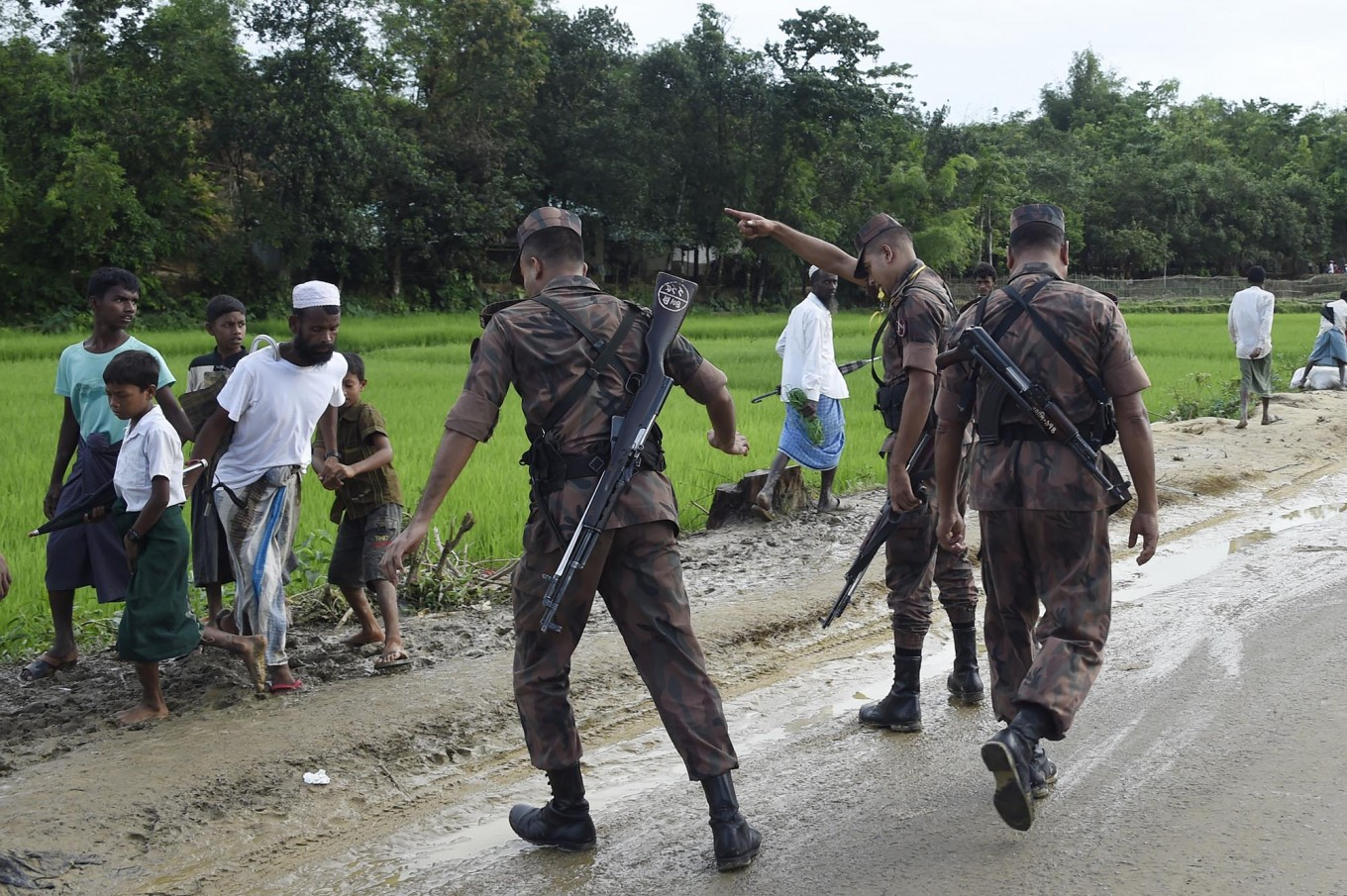 "Bangladesh Border Guard (BGB) attempts to clear Rohingya Muslim refugees off a road near Balukhali refugee camp near the Bangladehsi district of Ukhia on September 19, 2017. Aung San Suu Kyi said September 19 she does not fear global scrutiny over the Rohingya crisis, pledging to hold rights violators to account but refusing to blame the military for violence that has driven some 421,000 of the Muslim minority out of her country. In an address timed to pre-empt likely censure of Myanmar at the UN General Assembly in New York -- delivered entirely in English and aimed squarely at an international audience -- she called for patience and understanding of the unfurling crisis in her ""fragile democracy"". AFP/ Dominique Faget"