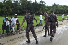 """Bangladesh Border Guard (BGB) attempts to clear Rohingya Muslim refugees off a road near Balukhali refugee camp near the Bangladehsi district of Ukhia on September 19, 2017. Aung San Suu Kyi said September 19 she does not fear global scrutiny over the Rohingya crisis, pledging to hold rights violators to account but refusing to blame the military for violence that has driven some 421,000 of the Muslim minority out of her country. In an address timed to pre-empt likely censure of Myanmar at the UN General Assembly in New York -- delivered entirely in English and aimed squarely at an international audience -- she called for patience and understanding of the unfurling crisis in her """"fragile democracy"""". AFP/ Dominique Faget"""