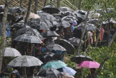 Rohingya Muslim refugees protect themselves from rain in Balukhali refugee camp near the Bangladesh town of Gumdhum on September 17, 2017.