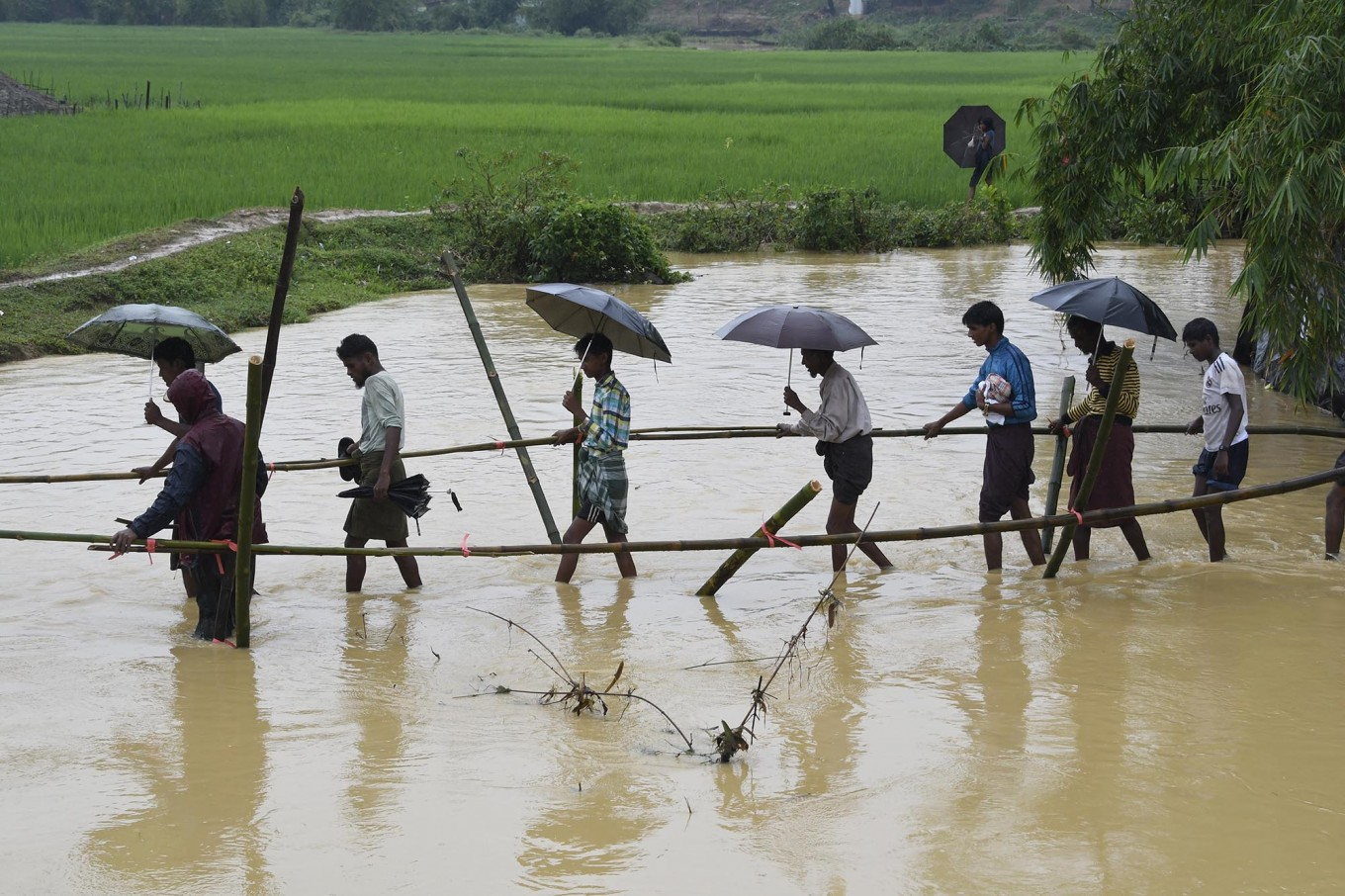 Rohingya Muslim refugees cross floodwater in Thyangkhali refugee camp near the Bangladesh town of Ukhia on September 17, 2017. Heavy monsoon rain heaped new misery September 17 on hundreds of thousands of Muslim Rohinyga stuck in makeshift camps in Bangladesh after fleeing violence in Myanmar, as authorities started a drive to force them to a new site. The United Nations says 409,000 Rohingyas have now overwhelmed Cox's Bazar since August 25 when the military in Buddhist-majority Myanmar launched operations in Rakhine state. AFP/ Dominique Faget