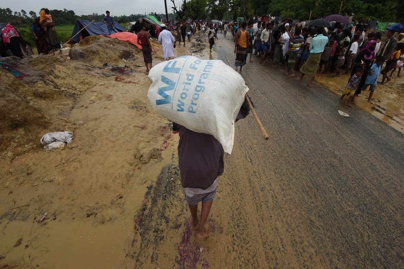 A Rohingya Muslim refugee carries a rice bag along a road near Balukhali refugee camp near the Bangladesh town of Gumdhum on September 17, 2017.
