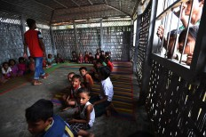 "Rohingya Muslim refugee children sit inside a school in Leda refugee camp near the Bangladeshi town of Teknaf on September 18, 2017. Pressure grew on Myanmar September 18 as a rights group urged world leaders to impose sanctions on its military, which is accused of driving out more than 410,000 Rohingya Muslims in an orchestrated ""ethnic cleansing"" campaign. The exodus of Rohingya refugees from mainly Buddhist Myanmar to neighbouring Bangladesh has sparked a humanitarian emergency. Aid groups are struggling to provide relief to a daily stream of new arrivals, more than half of whom are children. AFP/ Dominique Faget"
