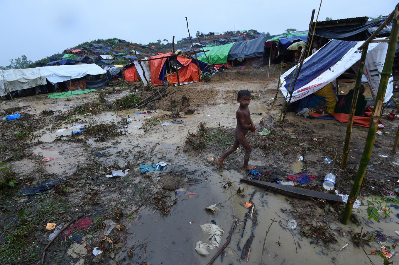 A Rohingya Muslim refugee child walks through Balukhali refugee camp near the Bangladesh town of Gumdhum on September 17, 2017. Heavy monsoon rain heaped new misery September 17 on hundreds of thousands of Muslim Rohinyga stuck in makeshift camps in Bangladesh after fleeing violence in Myanmar, as authorities started a drive to force them to a new site. The United Nations says 409,000 Rohingyas have now overwhelmed Cox's Bazar since August 25 when the military in Buddhist-majority Myanmar launched operations in Rakhine state. AFP/ Dominique Faget