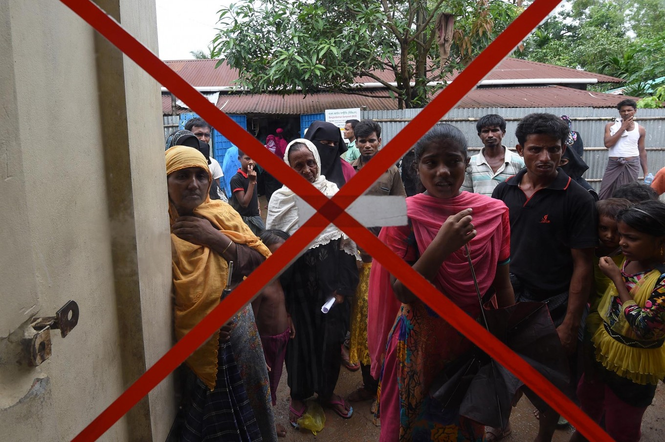 """Rohingya Muslim refugees wait for a consultation outside a clinic run by the International Organisation for Migration (IOM) in Leda refugee camp near the Bangladeshi town of Teknaf on September 18, 2017. Pressure grew on Myanmar September 18 as a rights group urged world leaders to impose sanctions on its military, which is accused of driving out more than 410,000 Rohingya Muslims in an orchestrated """"ethnic cleansing"""" campaign. The exodus of Rohingya refugees from mainly Buddhist Myanmar to neighbouring Bangladesh has sparked a humanitarian emergency. Aid groups are struggling to provide relief to a daily stream of new arrivals, more than half of whom are children. AFP/ Dominique Faget"""