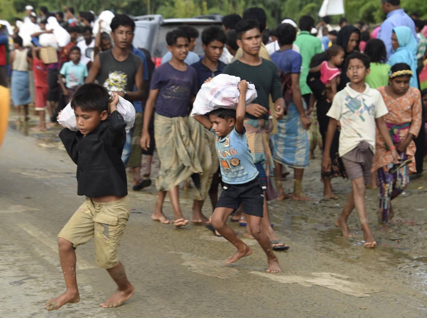 """Rohingya Muslim refugee children run after a distribution of supplies at Balukhali refugee camp near the Bangladehsi district of Ukhia on September 19, 2017. Aung San Suu Kyi said September 19 she does not fear global scrutiny over the Rohingya crisis, pledging to hold rights violators to account but refusing to blame the military for violence that has driven some 421,000 of the Muslim minority out of her country. In an address timed to pre-empt likely censure of Myanmar at the UN General Assembly in New York -- delivered entirely in English and aimed squarely at an international audience -- she called for patience and understanding of the unfurling crisis in her """"fragile democracy"""". AFP/ Dominique Faget"""