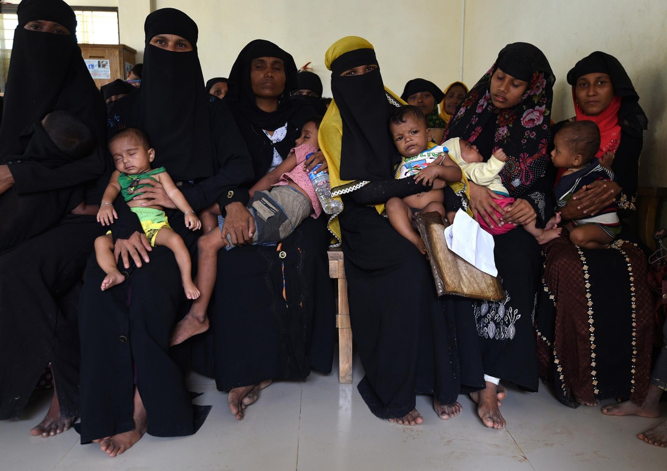 """Rohingya Muslim refugees wait with their children for a consultation at a clinic run by the International Organisation for Migration (IOM) in Leda refugee camp near the Bangladeshi town of Teknaf on September 18, 2017. Pressure grew on Myanmar September 18 as a rights group urged world leaders to impose sanctions on its military, which is accused of driving out more than 410,000 Rohingya Muslims in an orchestrated """"ethnic cleansing"""" campaign. The exodus of Rohingya refugees from mainly Buddhist Myanmar to neighbouring Bangladesh has sparked a humanitarian emergency. Aid groups are struggling to provide relief to a daily stream of new arrivals, more than half of whom are children. AFP/ Dominique Faget"""