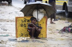 "A young Rohingya refugee shelters from the rain with an umbrella while sitting at Kutupalong refugee camp in the Bangladeshi locality of Ukhia on September 19, 2017. Pressure grew on Myanmar on September 18 as a rights group urged world leaders to impose sanctions on its military, which is accused of driving out more than 410,000 Rohingya Muslims in an orchestrated ""ethnic cleansing"" campaign. AFP/ Dominique Faget"