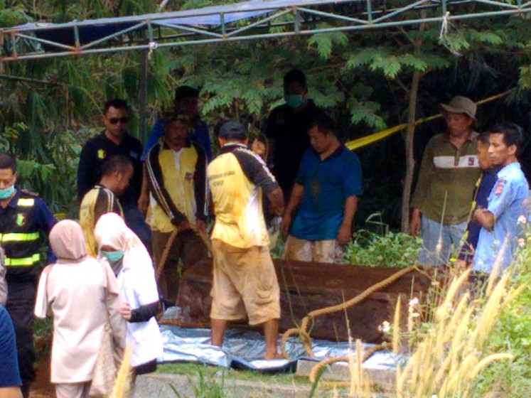 Under investigation: Workers exhume the grave of Hilarius Christian Event Raharjo on Sept. 19 for an autopsy to investigate the cause of his death.