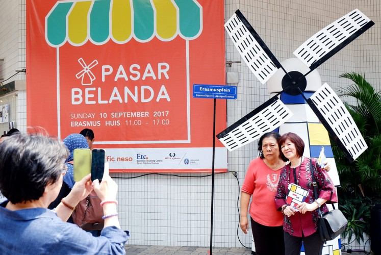 Mini-Holland: Visitors pose in front of a miniature of a Dutch windmill.