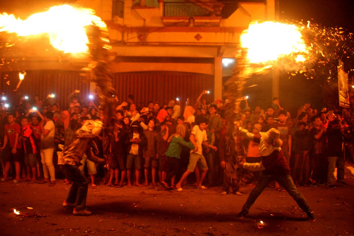Watch out: Spectators react as two combatants wield flaming torches. JP/ Maksum Nur Fauzan