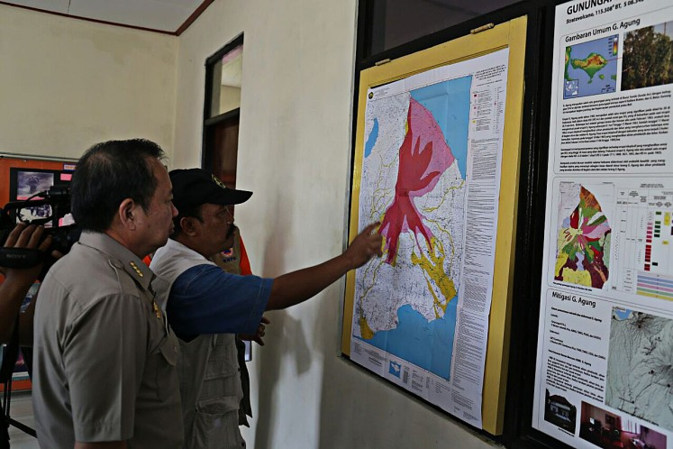 Get ready: An official at the observation post of Mount Agung, Bali, points out the risk zone of the volcano during the visit of National Disaster Mitigation Agency (BNPB) head Willem Rampangilei (left) on Sept. 20