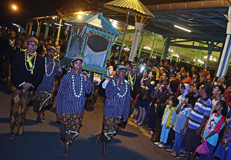 Surakarta royal servants carry a loji construction on a palanquin during the