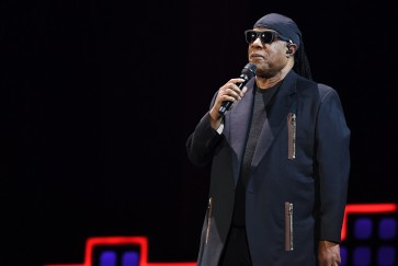 Stevie Wonder kneels as he leads anti-poverty concert