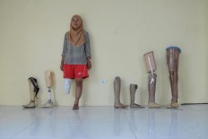 Paralympic athlete Ratifah poses in a line-up showing the variety of prosthetic limbs worn by athletes of the Indonesian delegation. JP/Maksum Nur Fauzan