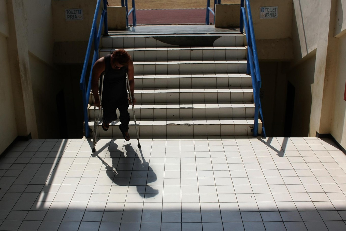 A paralympic athlete descends the stairs of the NPC training center after training exercises. JP/Maksum Nur Fauzan