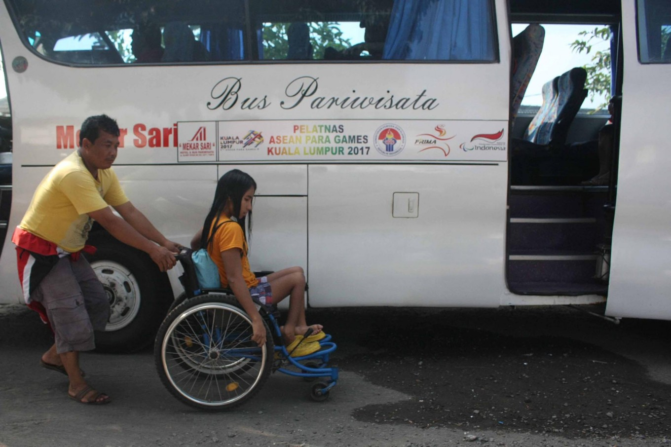 An NPC official pushes wheels an athlete to board the bus as the Indonesian delegation departs on their journey to the top. JP/Maksum Nur Fauzan
