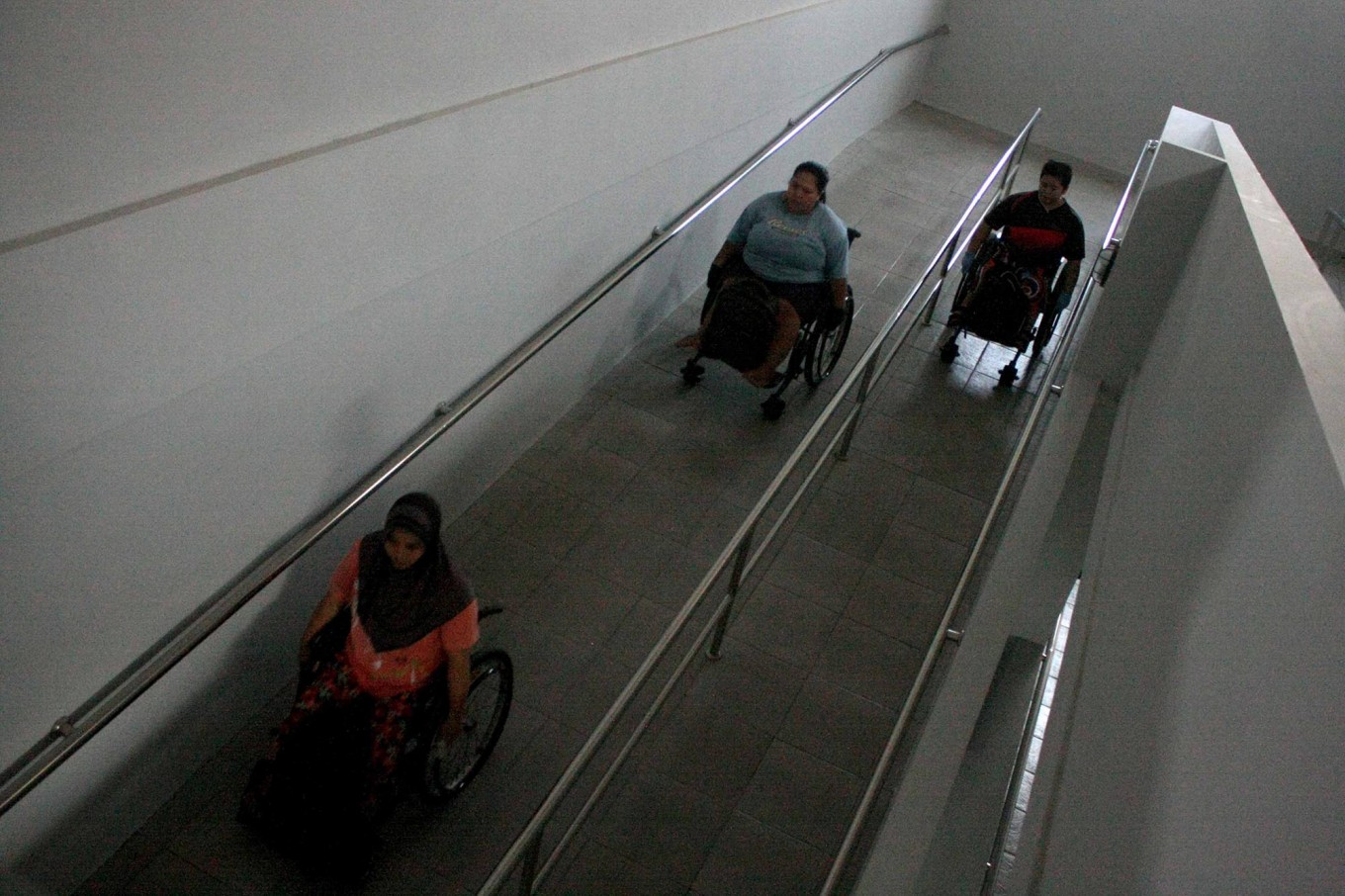 Three athletes maneuver their wheelchairs up a special ramp at the NPC Indonesia Office in