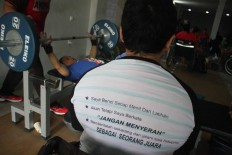 "An athlete wears a T-shirt with motivational words printed on it, which begins humorously with, ""I hate every minute of training...,"" and ends with the statement: ""I will suffer now and live the rest of my life as a champion."" JP/Maksum Nur Fauzan"