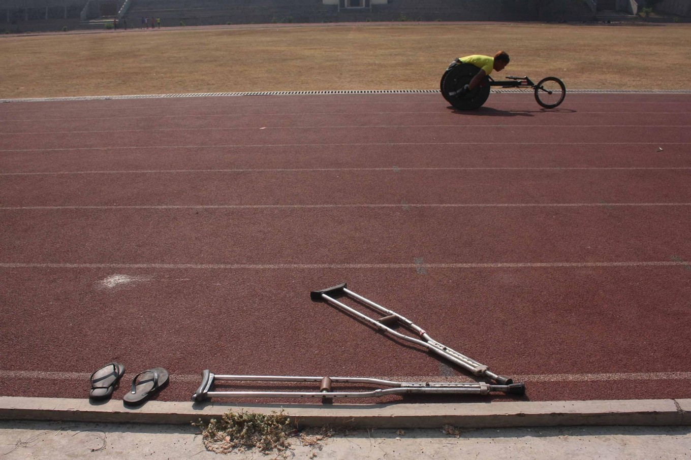 Crutches lie discarded alongside a track as a track-and- field athlete trains for the wheelchair race. JP/Maksum Nur Fauzan
