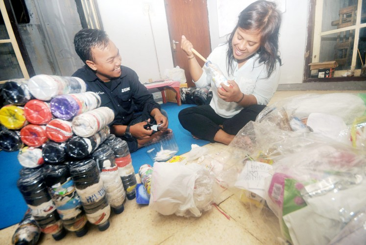 Reuse and recycle: Andri Saputro (left), a Banyuwangi university student guide, educates locals on how to process plastic waste into eco-bricks.